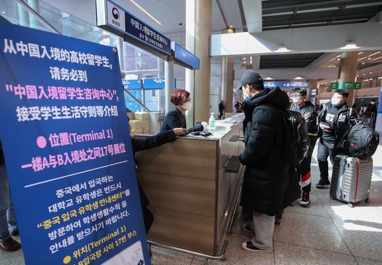 지난해 2월 인천국제공항으로 입국한 중국인 유학생들이 입국장 내 마련된 유학생센터에서 신종 코로나 바이러스 감염증(코로나19) 관련 안내를 받고 있다.   연합뉴스