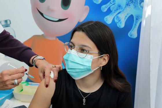 23일 이스라엘 텔아비브에서 한 청소년이 백신을 맞고 있다. 이스라엘은 접종 대상을 대학 입시를 앞둔 16~18세 청소년으로 확대했다. [신화통신=연합뉴스]
