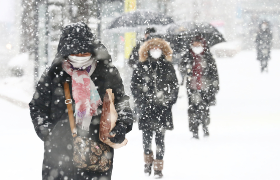 지난 18일 대설주의보가 내려졌던 대전 서구에서 눈을 맞으며 걸어가는 시민들. 기상청은 28일 전국에 눈이 내릴 것으로 예보했다. 뉴스1