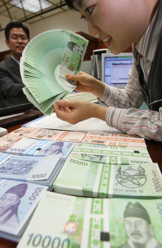 지난해 설을 앞두고 은행직원이 신권으로 바꿔주고 있다. 신한은행 본점에서 [중앙포토]