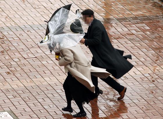 28일 오후 광주 서구 치평동에서 비를 동반한 강풍에 시민들의 손에 든 우산이 휘어지고 얼굴에 쓴 마스크가 벗겨지고 있다. 연합뉴스