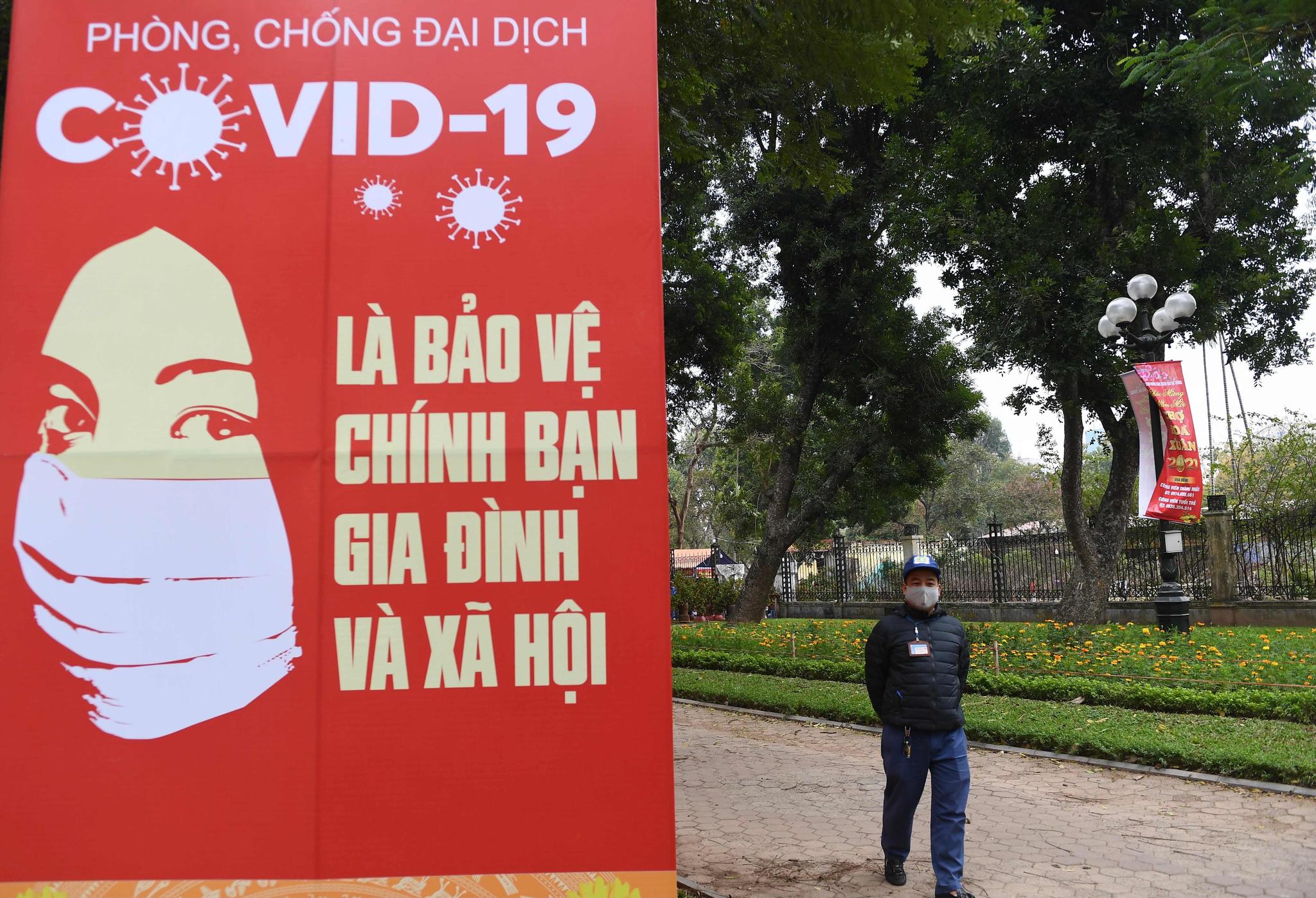 28일(현지시간) 베트남 하노이에서 신종 코로나바이러스 감염증(코로나19) 확산을 막기 위해 마스크를 쓴 한 남성이 공중보건캠페인 현수막 인근을 걷고 있다. AFP=연합뉴스
