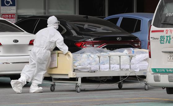지난해 신종 코로나바이러스 감염증(코로나19) 집단 감염이 발생한 서울 구로구 미소들요양병원에서 방호복을 입은 관계자들이 병실 거리두기를 위해 환자를 옆 건물로 이송하고 있다. 뉴스1