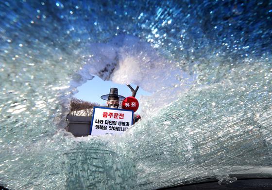 지난해 12월 17일 오전 서울 마포구 서부운전면허시험장에서 저승사자와 처녀귀신 등으로 분장한 모델들이 음주 교통사고 차량 앞에서 음주운전의 위험성을 알리고 있다. 뉴스1