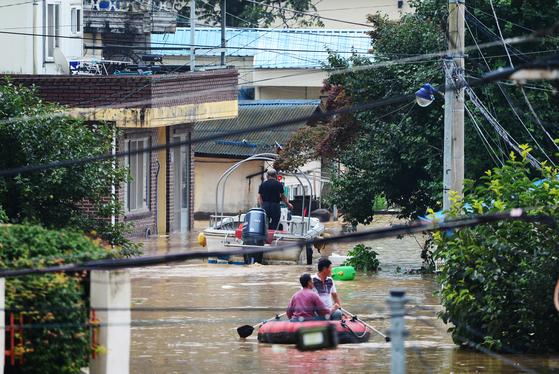 지난해 8월 8일 오후 경남 하동군 하동읍 인근에서 섬진강의 범람으로 마을이 침수되자 주민들이 고무보트를 타고 이동하고 있다. 뉴시스