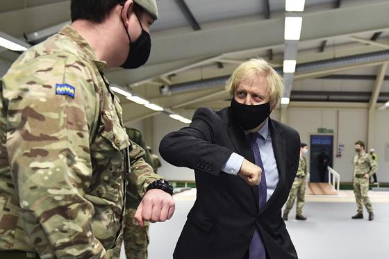 스코틀랜드를 방문한 보리스 존슨 영국 총리가 예방접종이 실시되는 군대를 찾아 팔꿈치 인사를 하고 있다. AP=연합뉴스
