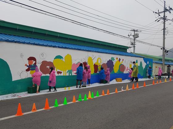 충북 옥천군 안내초교 아이들이 마을에 벽화를 그리고 있다. [사진 안내초]