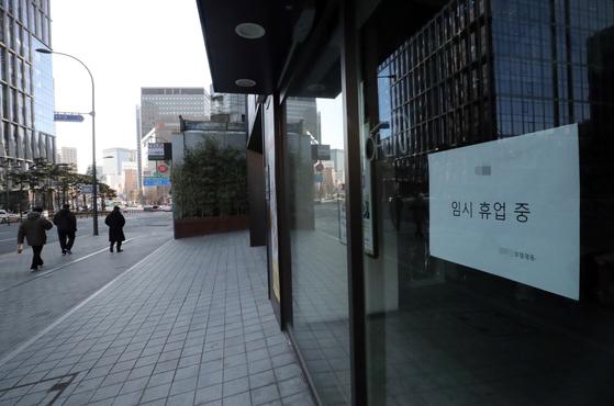 29일 코로나19 여파로 임시휴업 중인 서울 명동의 한 호텔에 휴업을 알리는 안내문이 걸려있다. [뉴스1]