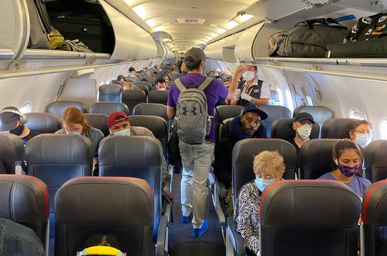 지난해 5월 3일 뉴욕에서 아메리칸 에어라인 항공편에 탑승 중인 승객들이 대부분 마스크를 쓰고 있다. 미국 질병통제예방센터(CDC)는 2월 1일 항공기, 기차, 지하철, 버스, 택시 등 모든 대중교통 탑승객에게 마스크 착용을 의무화했다.[AFP=연합뉴스]