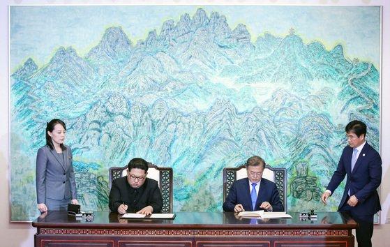 문재인 대통령(오른쪽 두 번째)과 김정은 북한 국무위원장(왼쪽 두 번째)이 2018년 4월 27일 남북 정상회담에서 한반도의 평화와 번영, 통일을 위한 판문점 선언문에 서명하고 있다. 왼쪽은 김 위원장 동생인 김여정 노동당 제1부부장, 오른쪽은 조한기 당시 청와대 의전비서관. [청와대사진기자단]