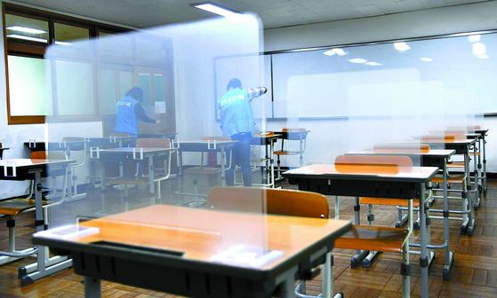대학수학능력시험을 일주일 앞둔 지난해 11월 26일 부산 남구 분포고등학교 교실에서 업체 관계자들이 반투명 아크릴 재질의 가림막을 책상에 설치하고 있다. 뉴시스