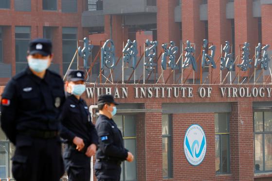 세계보건기구(WHO) 조사팀이 중국 우한 바이러스 연구소를 방문하는 동안 보안요원들이 밖을 감시하고 있다. [로이터=연합뉴스]