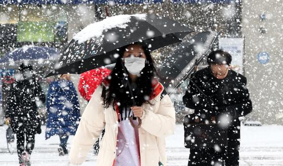 지난달 18일 대전 서구에서 시민들이 눈을 피해 발길을 재촉하고 있다. 뉴스1
