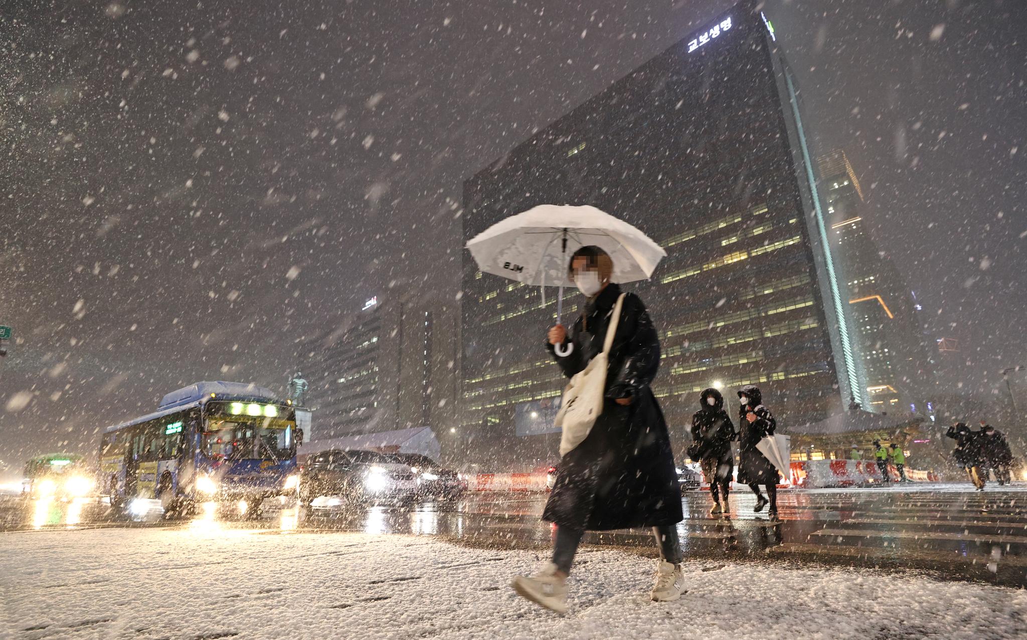 서울 전역에 대설주의보가 발효된 3일 오후 서울 광화문 광장에서 시민들이 눈을 맞으며 걸어가고 있다. 연합뉴스