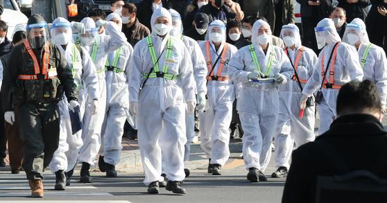 지난 12월 21일 충남 논산훈련소 입영심사대로 입소한 입영장병 중 11명이 신종 코로나바이러스 감염증(코로나19) 확진돼 같은날 입소한 1600명에 대해 2차 전수검사를 실시한 28일 오후 입영심사대 정문에서 방호복을 입은 군장병이 이동하고 있다. 뉴스1