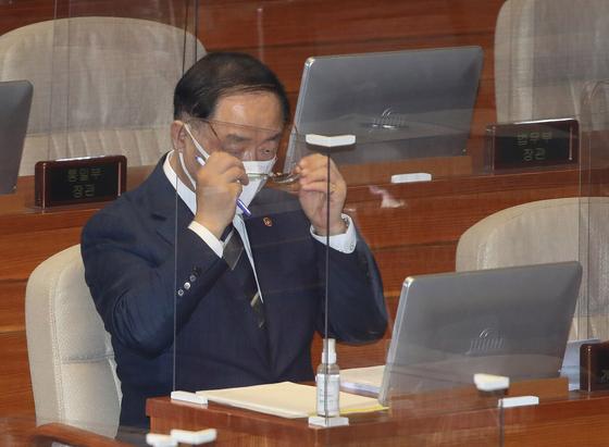 """홍남기 경제부총리 겸 기획재정부 장관이 5일 오후 서울 여의도 국회에서 열린 제384회국회(임시회) 제5차 본회의에서 안경을 고쳐쓰고 있다. 이날 홍 부총리를 향해 확장적 재정을 강조하는 질의가 쏟아졌지만, 그는 """"재정당국이 재정건전성을 보는 시각에 대해 이해 해주길 바란다""""는 기존 입장을 견지했다. 뉴스1"""