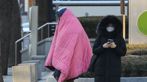 반짝 추위가 찾아 온 8일 오전 서울 시내에서 한 시민이 이불을 쓰고 지나가고 있다. 연합뉴스
