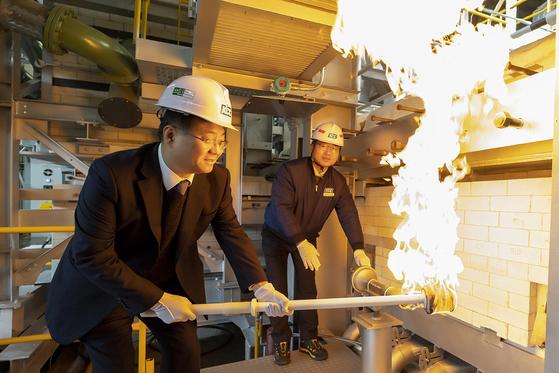 정몽진 KCC 회장(왼쪽)이 2019년 문막공장 글라스울 2호기 화입식에서 용해로에 불씨를 넣고 있다. 연합뉴스