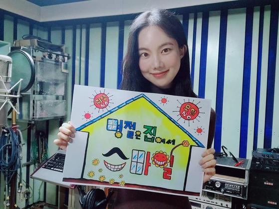 가수 김나희씨가 '명절은 집에서, 스마일' 그림판을 들고 SNS를 통해 인증하는 모습. [사진 칠곡군]