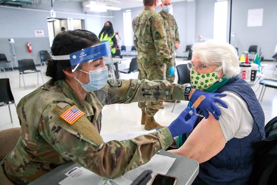 미국 일리노이주의 리버 그로브에 설치된 신종 코로나바이러스 감염증(코로나19) 백신 접종소에서 3일(현지시간) 주 방위군 부사관이 주민의 팔에 백신을 접종하고 있다. [AFP]
