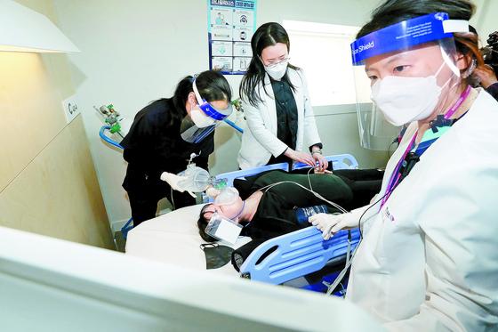 9일 서울 중구 국립중앙의료원 중앙예방접종센터에서 진행된 코로나19 백신 접종 모의훈련에서 의료진들이 백신 접종 후 이상증세를 보인 참가자를 응급처치하고 있다. 연합뉴스