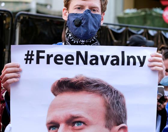 """미국에서 러시아 야권 운동가 알렉세이 나발니 석방 운동이 벌어졌다. 캘리포니아에서 한 시위자가 """"나발니를 석방하라""""라는 문구가 쓰여진 나발니의 사진을 들고 있는 모습. [로이터=연합뉴스]"""