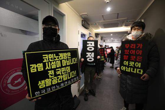 자영업자비대위 회원들이 10일 오전 0시 서울 서대문구의 한 코인노래연습장에서 오후 9시 영업시간 제한 폐지를 촉구하며 개점시위를 벌이고 있다. [뉴스1]
