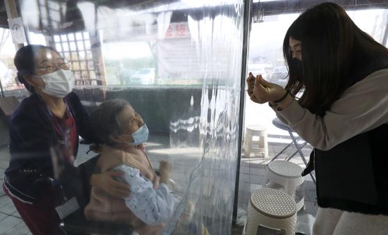 설날인 12일 오후 울산시 울주군 이손요양병원에 설치된 비닐 면회실에서 며느리가 비닐막 너머 앉은 시어머니에게 손하트를 만들어 보이고 있다. 뉴스1