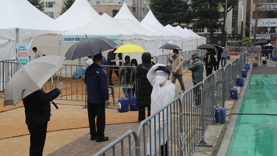 설 연휴 마지막 날인 14일 부산 부산진구 놀이마루 운동장에 설치된 임시 선별검사소에 업무 복귀를 앞두고 코로나 19 검사를 받으려는 시민들이 몰려 우산을 쓴 채 차례를 기다리고 있다. 송봉근 기자