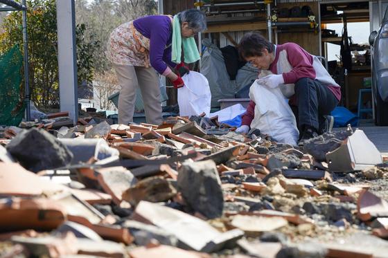 14일 일본 후쿠시마현 소마시에서 주민들이 13일 밤 일어난 지진으로 깨진 기와를 치우고 있다. [EPA=연합뉴스]