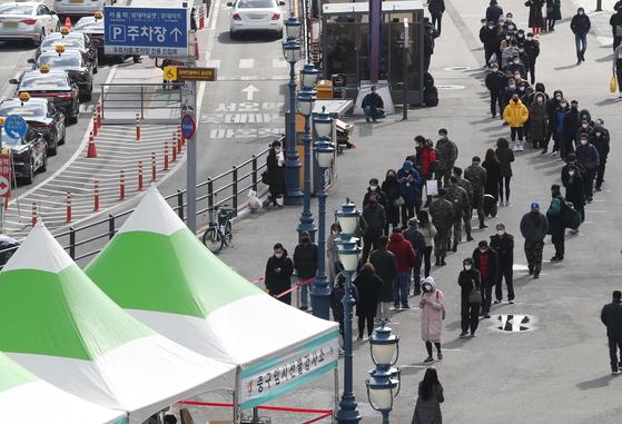 15일 오후 서울역에 마련된 코로나19 임시 선별검사소를 찾은 시민들이 길게 줄을 서 있다. 연합뉴스