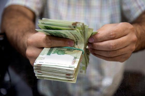 한국 시중 은행에 묶여 있는 이란의 자금을 돌려주기 위해 외교부가 워킹그룹을 조직했다. 사진은 2019년 8월 1일 이란 테헤란의 한 세일즈맨이 이란 화폐를 세고 있는 장면. [로이터=연합뉴스]