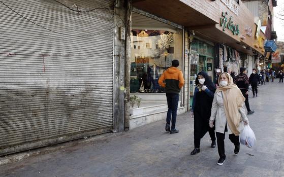 지난해 3월 12일 이란 테헤란의 한 전통시장 근처를 지나고 있는 사람들. 이날 이란은 IMF에 긴급 자금을 요청했다. [AFP=연합뉴스]