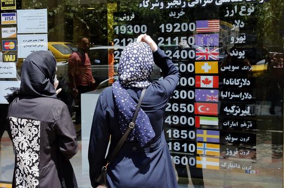 이란 화페 가치가 미국의 제재와 코로나19의 영향으로 사상 최저 수준을 기록했다. 사진은 지난해 6월 22일 이란 테헤란에서 환율을 살펴보고 있는 이란 여성들. [EPA=연합뉴스]