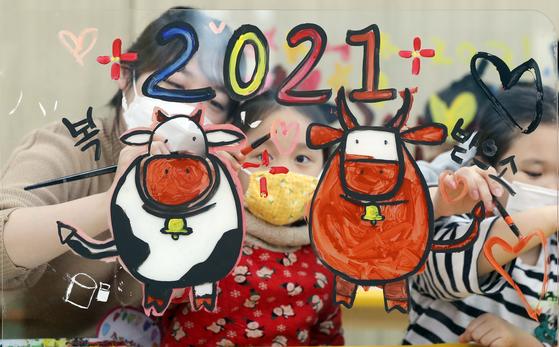 지난달 6일 오후 광주 북구청직장어린이집에서 신축년 새해를 맞아 어린이들이 선생님들과 함께 투명 아크릴판에 소를 그리고 색칠하는 놀이를 하고 있다. 사진은 기사 내용과 관련 없음. [연합뉴스]