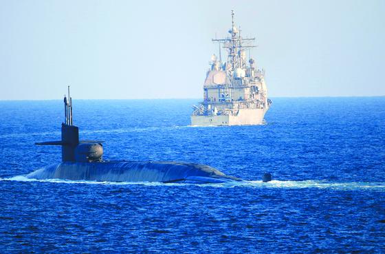 미국의 오하이오급 핵잠수함 조지아호( 왼쪽)와 순양함 포트 로열호 가 페르시아만의 원유 수송로인 호르무즈 해협을 항해하는 사진이 지난해 12월 21일(현지시간) 공개됐다. [AP=연합뉴스]
