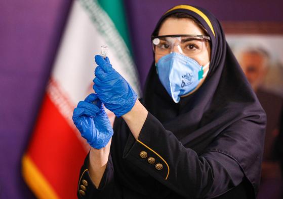 지난해 12월 29일 이란의 한 의료 관계자가 임상 1상 단계인 자국 백신을 실험하기 위해 주사를 준비하고 있다.의 개발위한 임상 1상에서 개발한 백신 투여를 실험하고 있다. [AFP=연합뉴스]