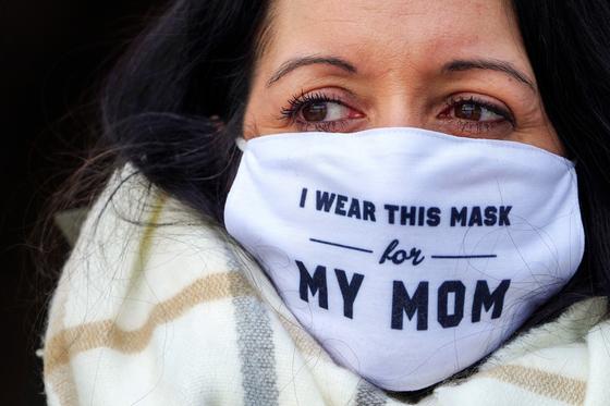 """2월 10일 뉴욕 브루클린에서 한 여성이 """"나는 엄마를 위해 마스크를 쓴다""""라고 새겨진 마스크를 착용한 모습. 로이터=연합뉴스"""
