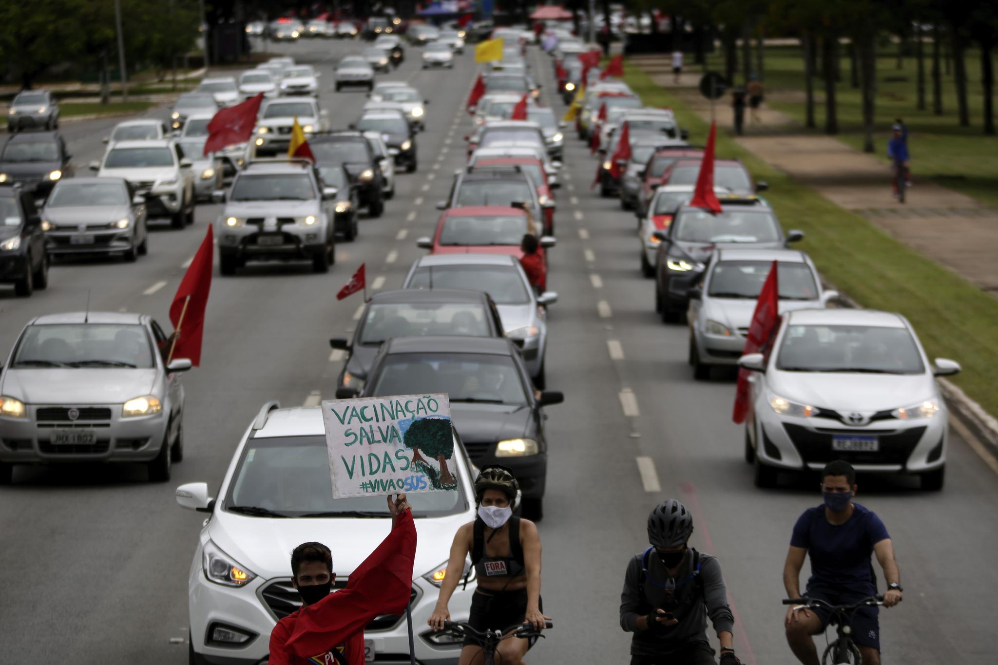 """시위대가 21일 브라질리아에서 """"백신이 생명을 살린다""""는 피켓을 앞세우고 가두시위를 벌이고 있다. AP=연합뉴스"""