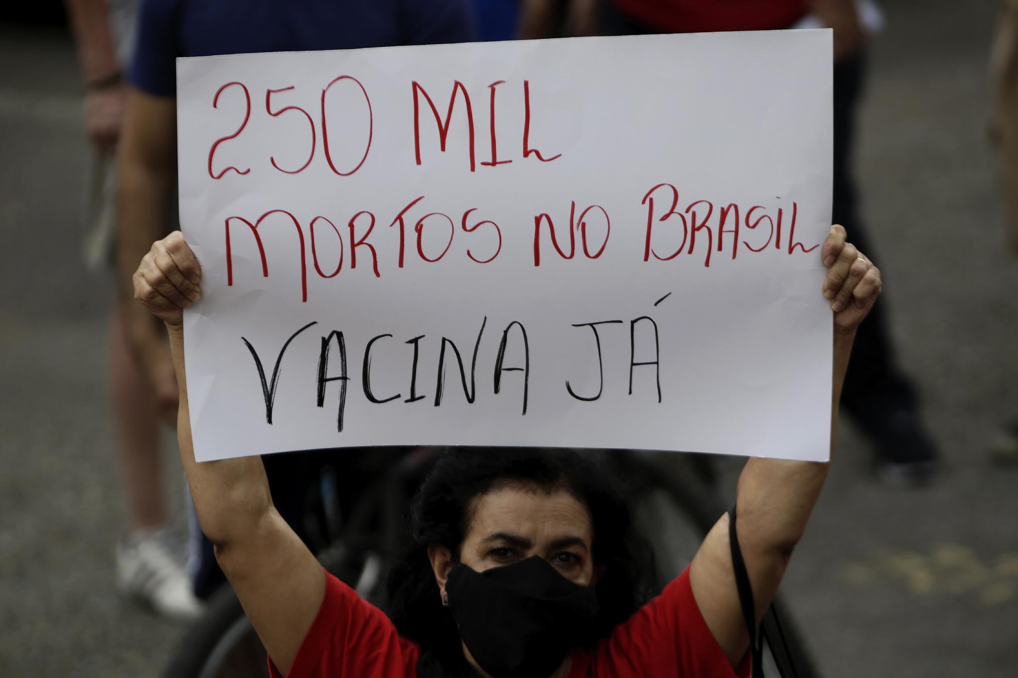 """21일 시위에 참여한 한 여성이 """"브라질에서 25만명이 사망했다. 지금 백신이 필요하다""""고 쓴 플래카드를 들고 있다. AP=연합뉴스"""