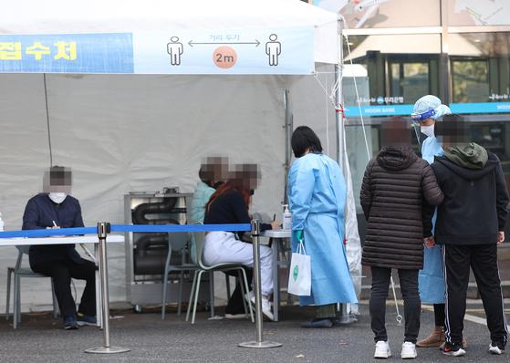 국내 신종 코로나바이러스 감염증(코로나19) '3차 대유행'의 여파가 곳곳에서 이어지는 가운데 21일 오후 서울 양천구보건소에 마련된 선별진료소에서 시민들이 검사를 받기 위해 기다리고 있다. 연합뉴스