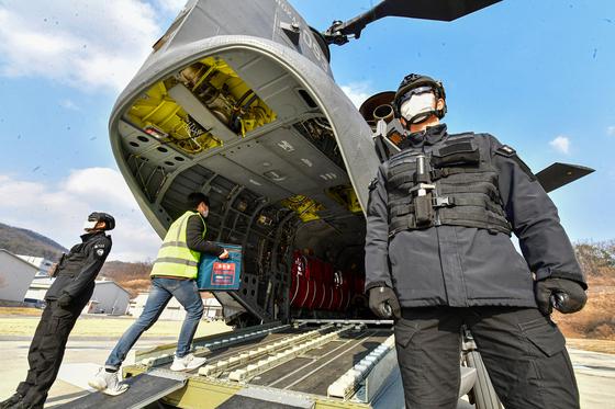 19일 오후 경기도 이천시 특수전사령부 헬기장에서 열린 '백신 유통 제2차 범정부 통합 모의훈련'에서 운송 관계자가 치누크헬기(CH-47D)에 백신 모형을 운반하고 있다. 사진공동취재단