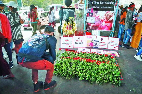 21일 미얀마 최대 도시 양곤에서 한 시민이 쿠데타 반대 시위 도중 머리에 총탄을 맞고 뇌사 상태에 빠졌다 열흘 만에 숨진 20세 여성의 추모 제단에 헌화하고 있다. 미얀마에선 군경이 시위대에 발포해 4명 이상이 숨졌다. [AP=연합뉴스]