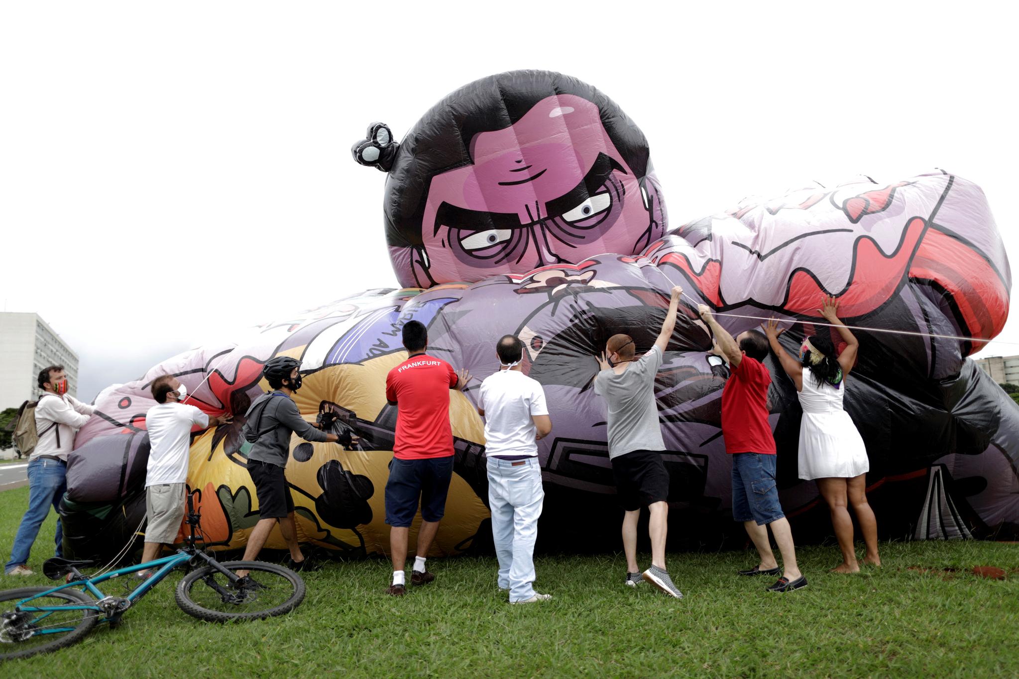 보우소나루 대통령 탄핵을 요구하는 브라질 사회단체 회원들이 21일 수도 브라질리아에서 보우소나루 대통령의 얼굴을 그린 풍선에 공기를 주입하고 있다. 로이터=연합뉴스