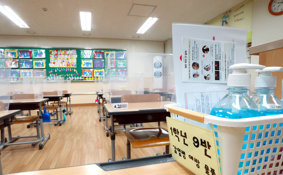 서울 서초구의 한 초등학교 교실에 방역 물품이 비치돼 있다. 비대면 수업에 따른 부작용을 우려하는 학부모들은 교문을 열기를 바라고 있다. [연합뉴스]