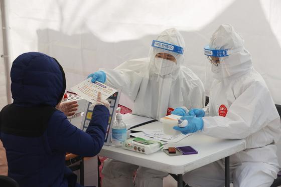 23일 오후 서울의 한 임시선별진료소에서 의료진이 코로나19 관련 검사 안내를 하고 있다. 연합뉴스