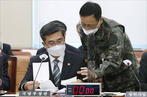 서욱 국방부 장관이 23일 국회에서 열린 국회 국방위원회 전체회의에서 군 관계자와 대화를 하고 있다. [중앙포토]
