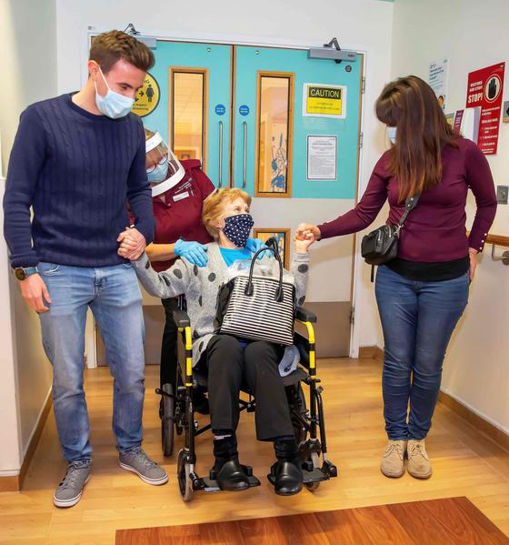 세계에서 처음으로 화이자 코로나19 백신을 맞은 마거릿 키넌(90) 할머니가 지난해 12월 9일(현지시간) 딸 수와 손자 코너의 손을 잡고 영국 코번트리 병원에서 퇴원하고 있다. [AFP]