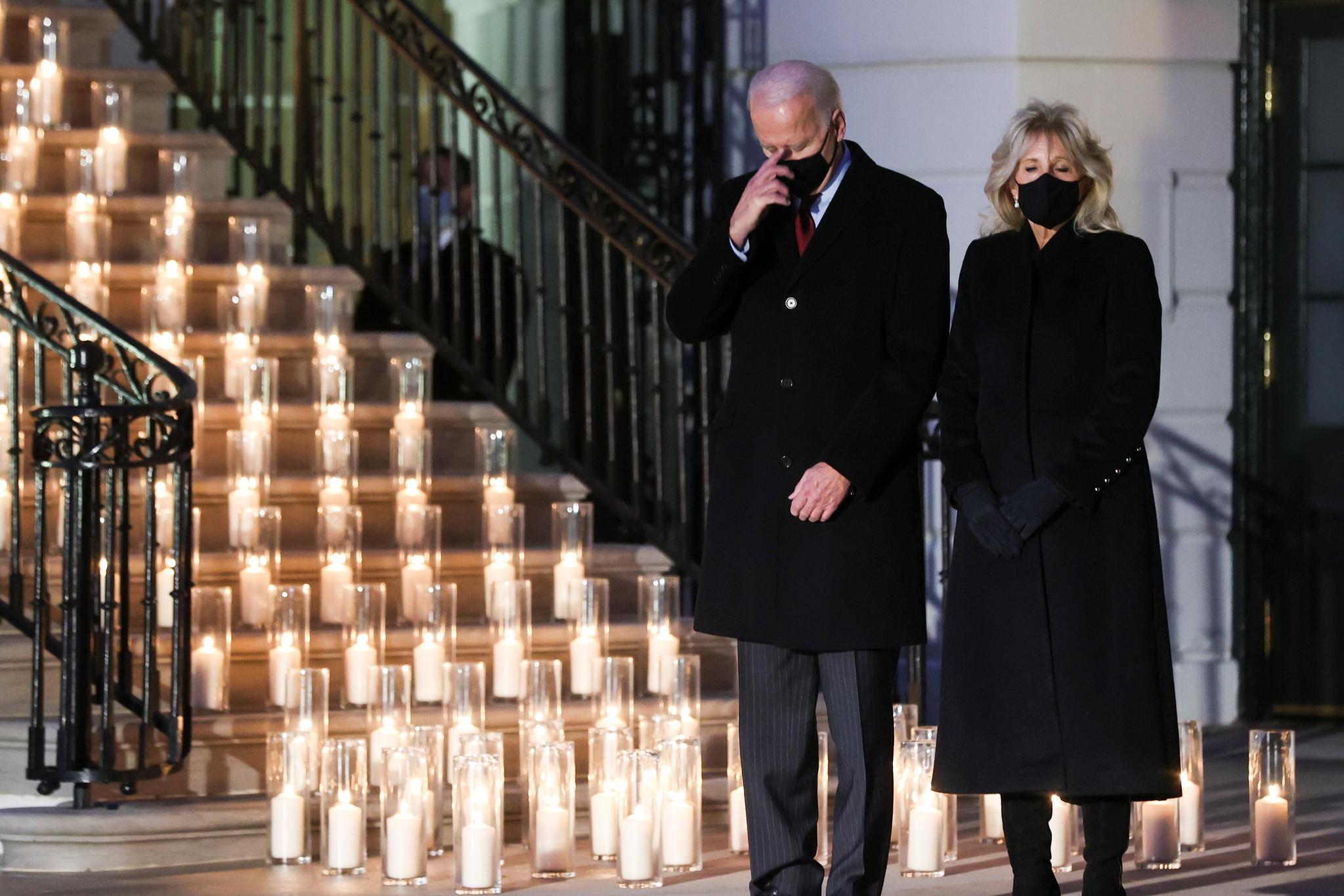 바이든 미국 대통령과 부인 질 바이든 여사가 22일 저녁 백악관에서 열린 코로나 19 희생자 50만명을 추모하는 촛불 점화 행사에 참석해 희생자를 추모하고 있다. 로이터=연합뉴스