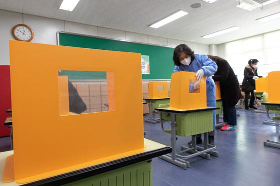 2021학년도 새학기 개학을 일주일가량 앞둔 지난 23일 서울 시내의 한 초등학교 교실에서 교직원들이 책상 칸막이를 소독하고 있다. 뉴스1